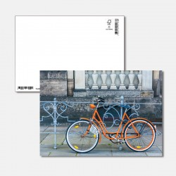 Oranges Fahrrad am Zaun